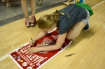 Emma signs the Capitol Hill History Day banner, one of a dozen kids from the school to ever make it to nationals.